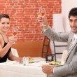 Couple drinking wine in restaurant - Stock Photo