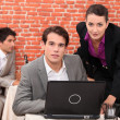 Young co-workers watching laptop — Stock Photo #7550713