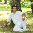 Man in white sitting under a tree — Stock Photo