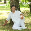 Stock Photo: Man in white sitting under a tree