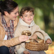 Young woman and little girl with basket of mushrooms — Stock Photo