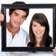 Couple holding empty picture frame — Stock Photo #7551051