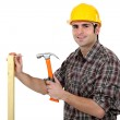 Carpenter driving a nail in a beam, studio shot — Stock Photo #7551763
