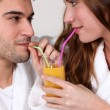 Stock Photo: Couple sharing glass of orange juice