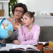 ストック写真: Womhelping her granddaughter complete her geography homework
