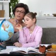 Stock Photo: Womhelping her granddaughter complete her geography homework