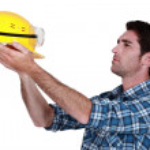 Man holding up a construction helmet — Stock Photo