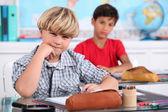 Estudiantes sentados en la mesa en el salón de clases — Foto de Stock
