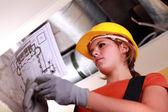 Junge weibliche arbeiter lesen plan — Stockfoto