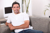 35 years old man sitting in a comfortable couch — Stock Photo