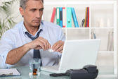 Office worker taking medication for headache — Stock Photo