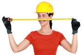 Tradeswoman extending a measuring tape — Stock Photo