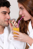 Couple sharing a glass of orange juice — Stock Photo