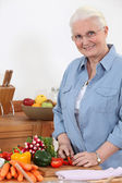 Elderly woman chopping vegetables — Stock Photo