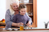 Little girl cooking with grandmother — Stock Photo
