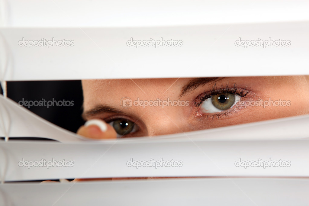 Closeup of a woman's eyes spying through blinds — Stock Photo #7551956
