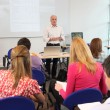 Stock Photo: Teacher stood at front of class room