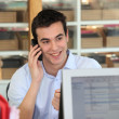 Stock Photo: Male office worker speaking to customer on telephone