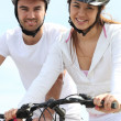 Young couple riding bicycles — Stok Fotoğraf #7606965