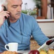 Stock Photo: Mature man having breakfast and reading newspaper