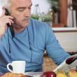 Mature man having breakfast and reading newspaper — Stock Photo