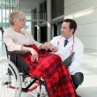Doctor talking to an elderly woman in a wheelchair — Stock Photo