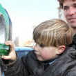 Little boy putting a glass bottle into a recycling bin - Stock Photo