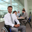 Businessman in wheelchair with colleagues in background — Stock Photo