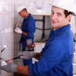 Electricians wiring a large white tiled room — Stock Photo