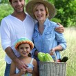Parents and young daughter with basket of vegetables - Stock Photo