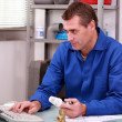 Plumber's merchant looking up details for thermostatic valve on — Stock Photo #7607727