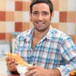 Man dunking a croissant into a cafe au lait at breakfast time — Stock Photo #7607734