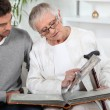 Elderly person looking at photos with son — Stock Photo #7607852