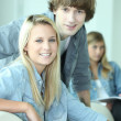 Three teenagers sat working together — Stockfoto