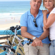 Royalty-Free Stock Photo: A middle aged couple biking by the seashore.