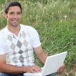Mlooking at his laptop in field — Stock Photo #7608043