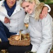 Couple gathering mushrooms in basket - Stock Photo
