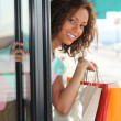 Woman with shopping bags coming out of shop — Stock Photo