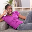 Royalty-Free Stock Photo: Afro-American woman on the phone laid on a sofa