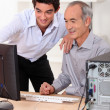 Stock Photo: Younger and older men looking at computer