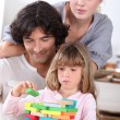 Parents building blocks with their daughter — Stock Photo