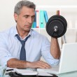 Stock Photo: Businessmmaking exercises in his office