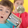 Stock Photo: Children communicating with tin cans
