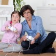 Royalty-Free Stock Photo: A mother and her daughter playing video game.