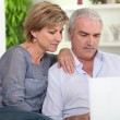 Middle-aged couple looking at their laptop — ストック写真