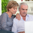 Middle-aged couple looking at their laptop — Stock Photo