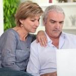 pareja de mediana edad mirando su ordenador portátil — Foto de Stock