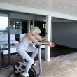 Stock Photo: Womexercising on stationary bicycle