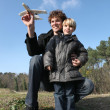 Father and son playing with an aeroplane — Stock Photo