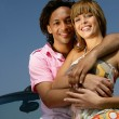 Smiling couple embraced in front of a car — Stock Photo